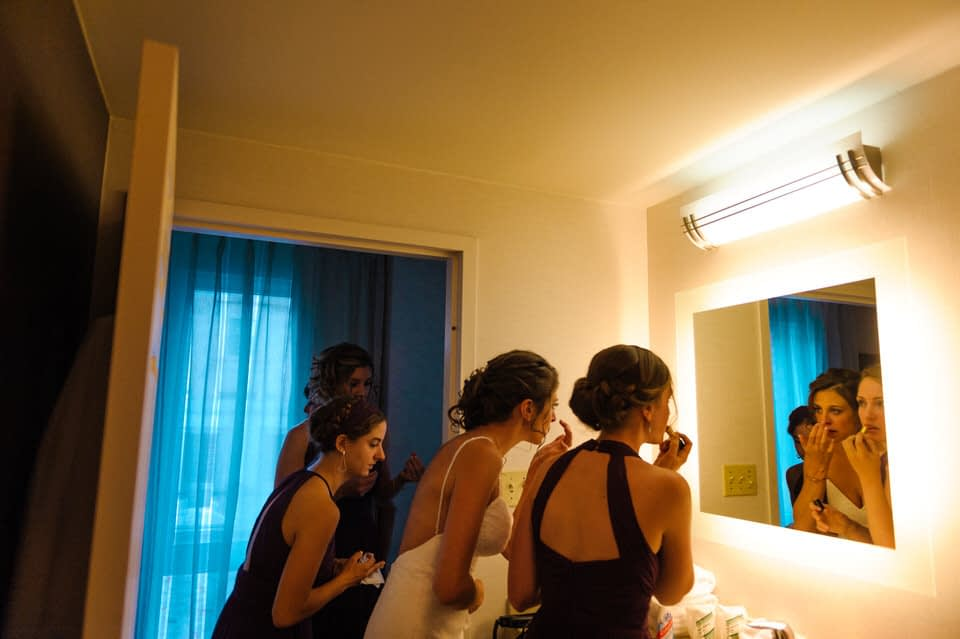 Bridesmaids and bride getting ready in the bathroom of the hotel