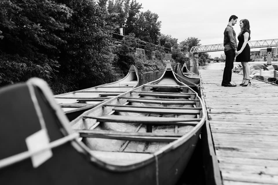 Engaged couple on a dock near canoes