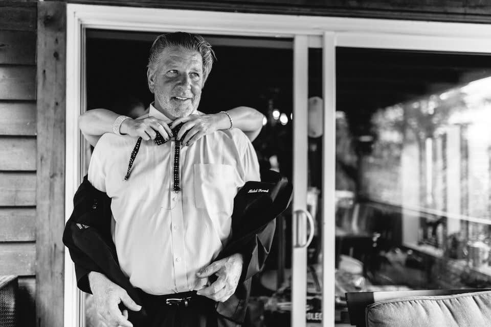Hands reaching around man's neck as he gets a bow tie on
