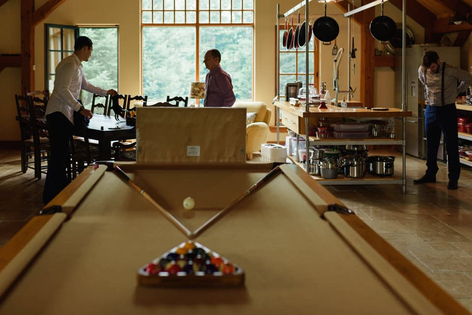 Wide room photo of a cabin with pool table and groom getting ready