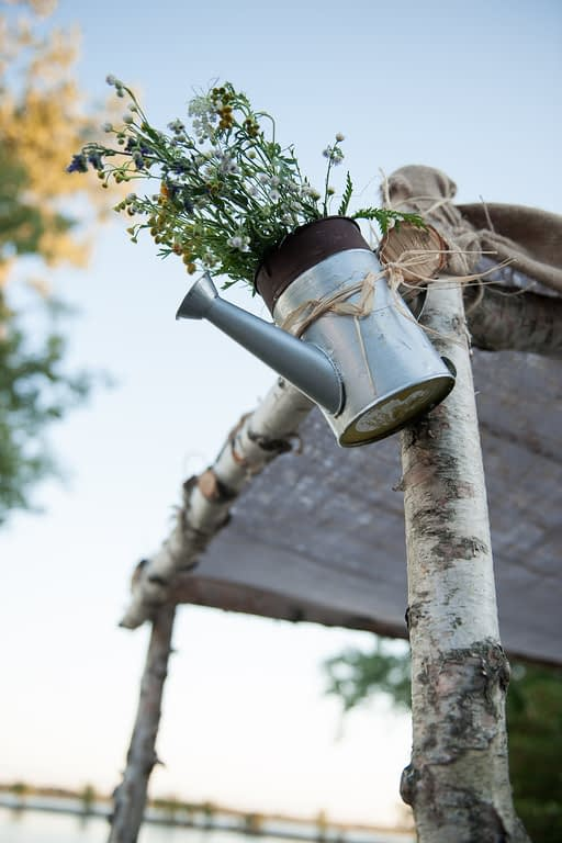Rustic wedding decoration of watering can on huppa