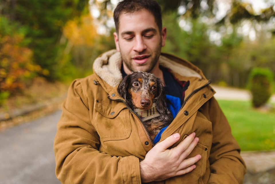 Man carrying his dog wrapped in his coat