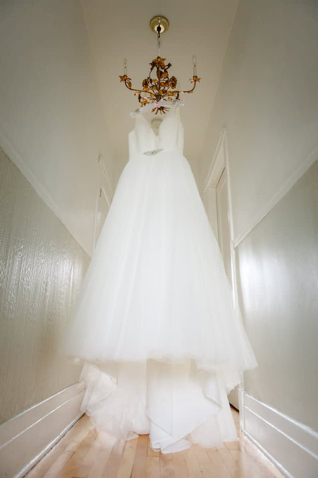 White wedding dress hanging from a vintage chandelier