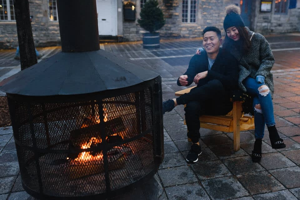 Couple sitting in chair near outdoor fire pit in Montreal