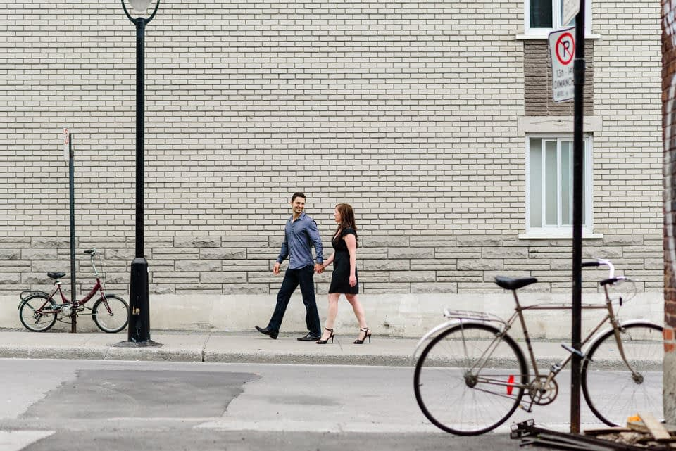 Couple walking along street past bicycles in Little Burgundy