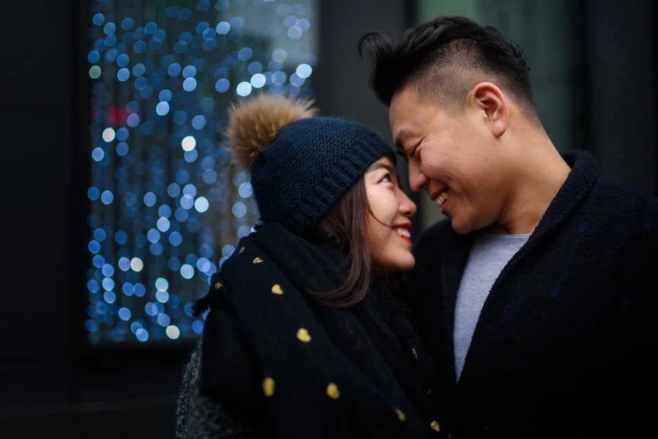 Couple smiling at each other with fairy lights behind them