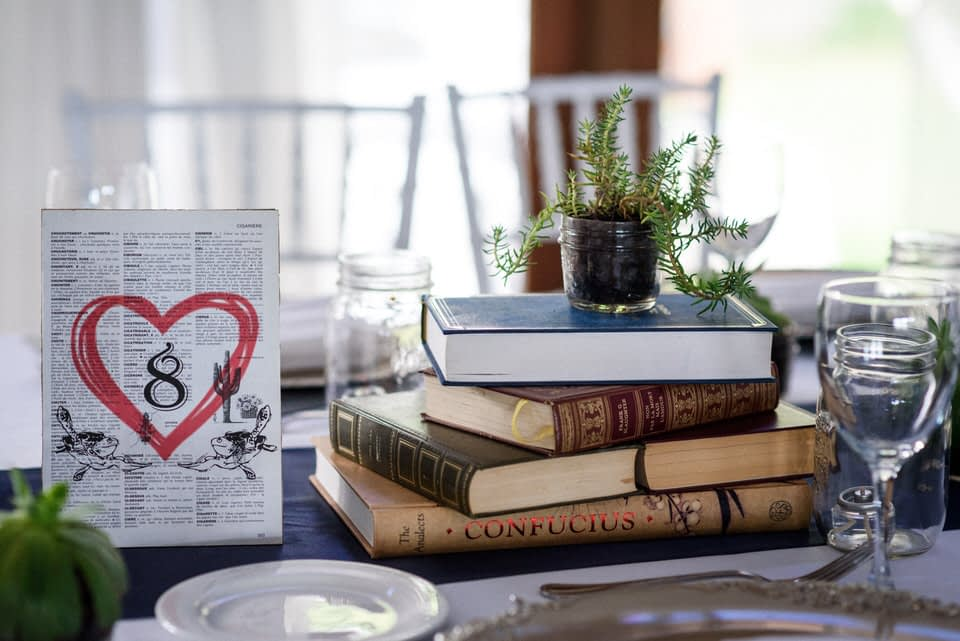 Cute nerdy wedding decorations featuring books and succulents