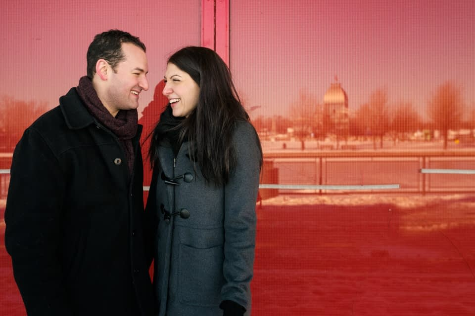 Couple smiling at each other standing next to a glass wall with the reflecion of Old Montreal Port