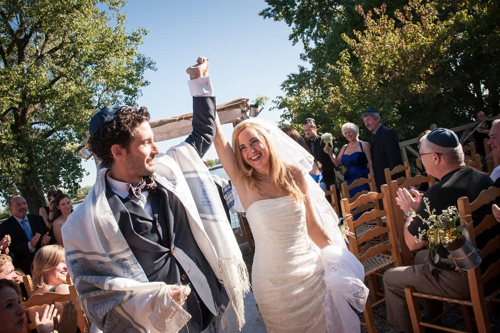 Happy bride and groom running from wedding ceremony