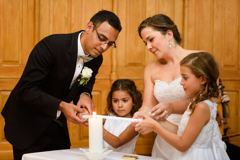 Family lighting candles at wedding