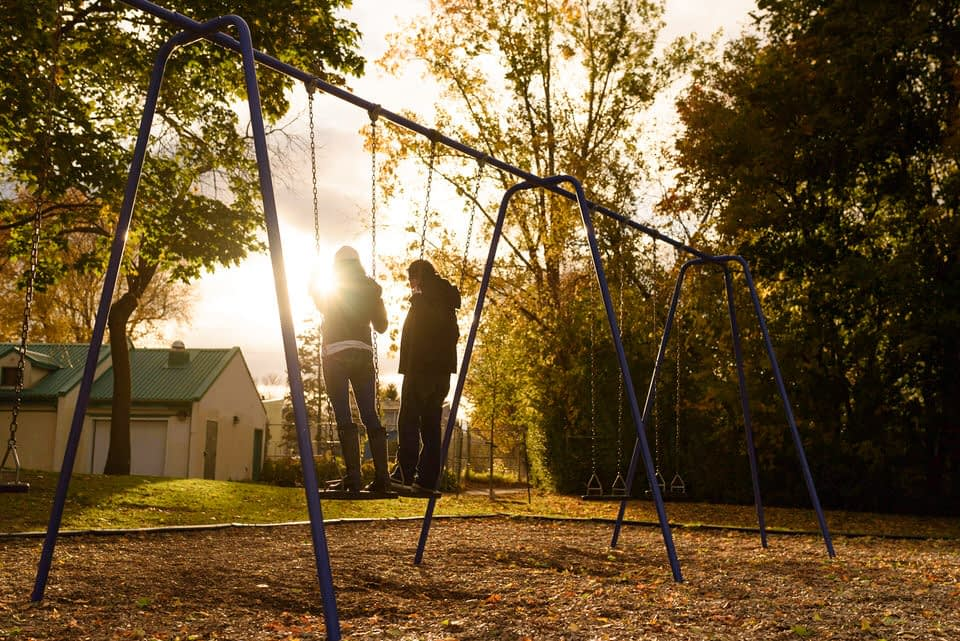 Couple swinging in a park on the sunset