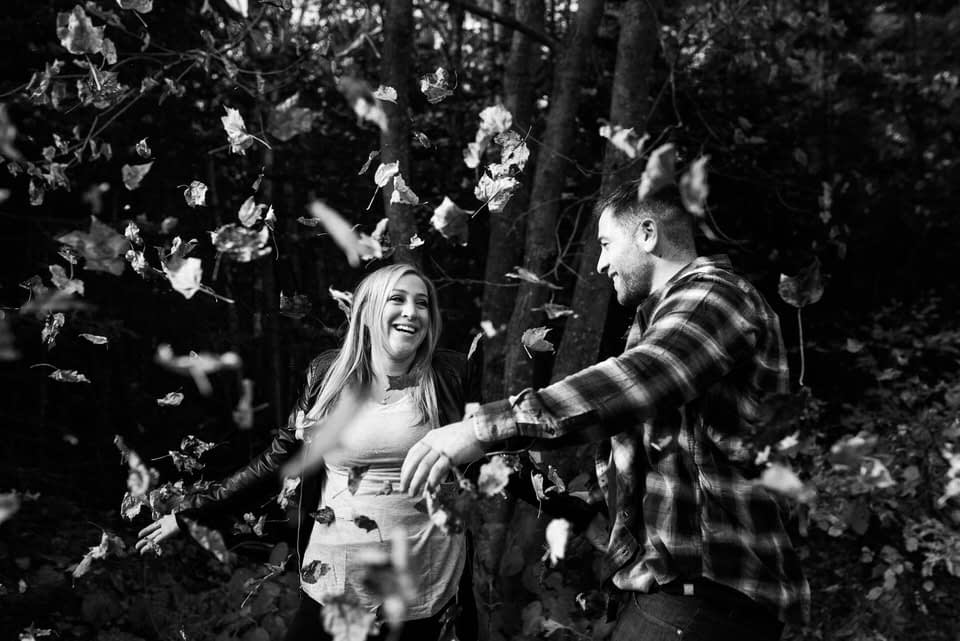 Couple throwing autumn leaves into the air