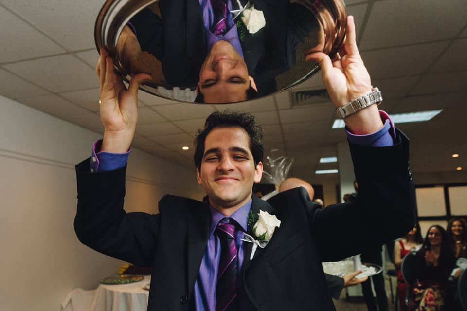 Groomsman carrying tray during Persian wedding in Quebec