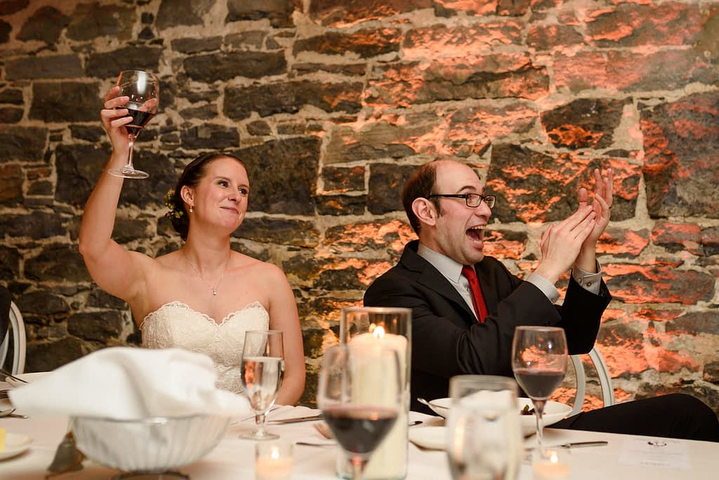 Bride raising her glass while groom laughs and claps