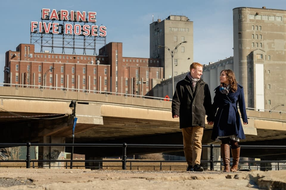 Engaged couple walking at Peel Bassins with Farine Five Roses sign behind them