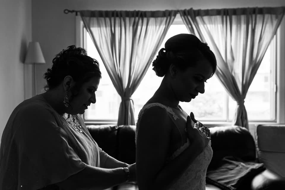Mother attaching bride's dress