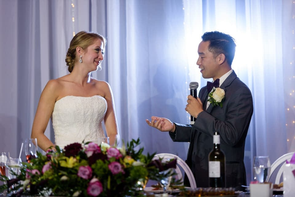 Groom giving speech and bride smiling at him