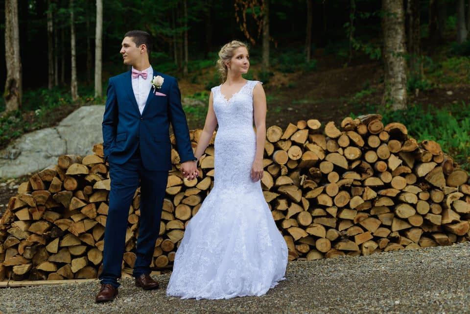 Wedding portrait in front of pile of wooden logs