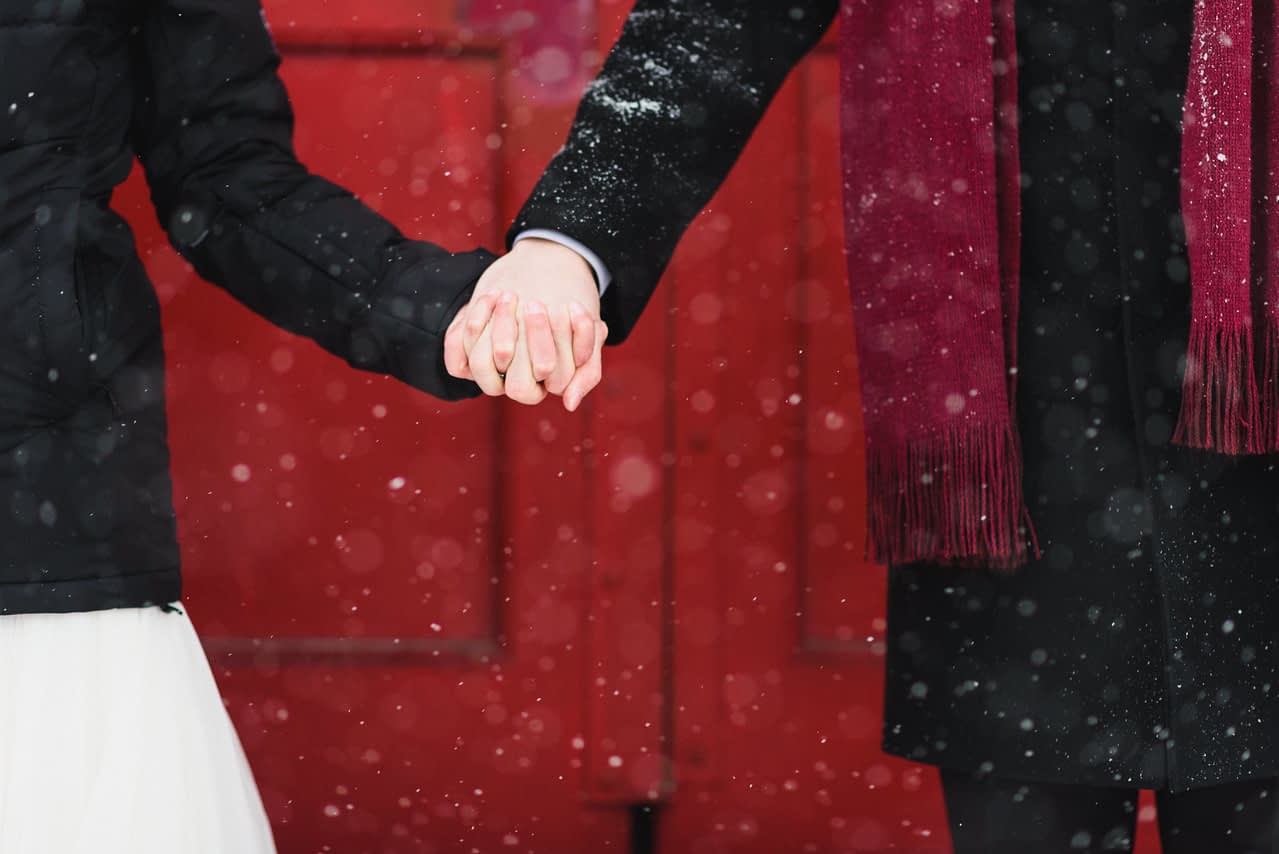 Close up of bride and groom holding hands in front of red door