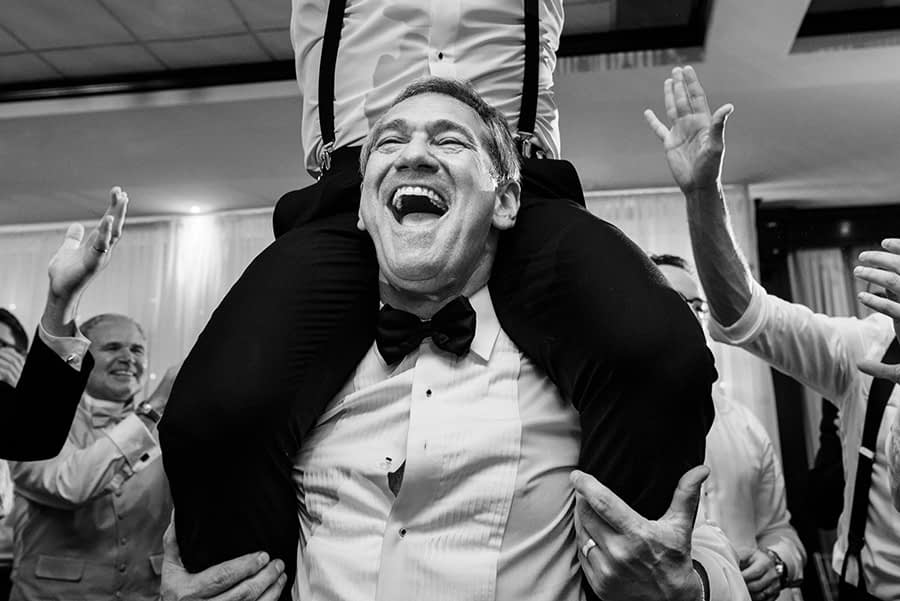 Candid photo of the father of the groom lifting his son on his shoulders, during the hora, as his shirt button pops and a huge grin covers his face