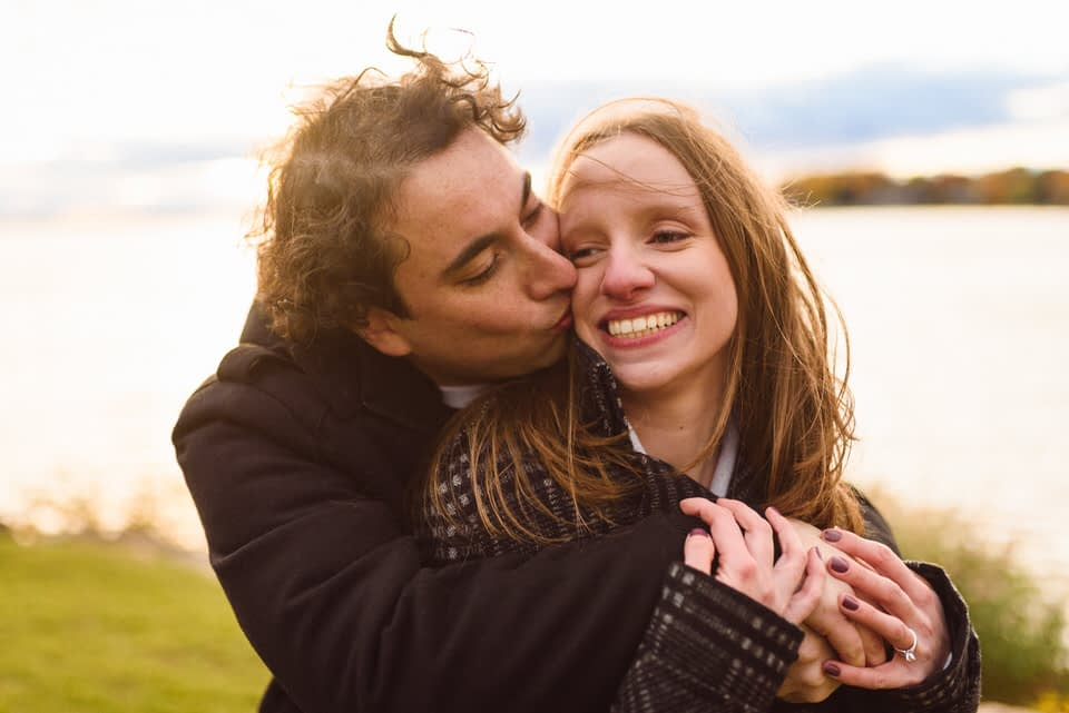 Guy kissing fiancée's cheek while holding her