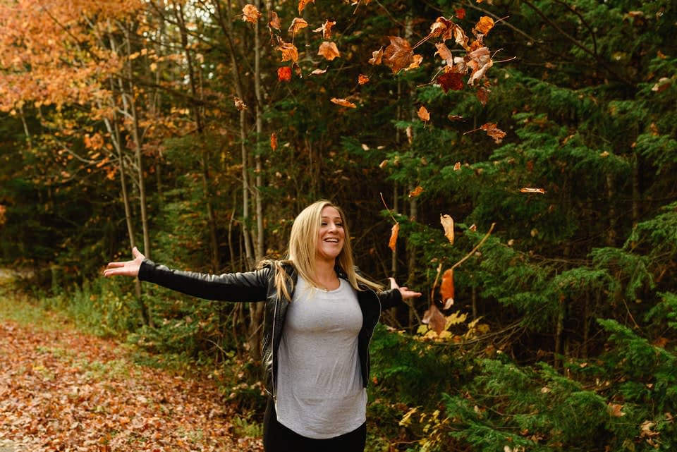 Woman throwing fall leaves into the air