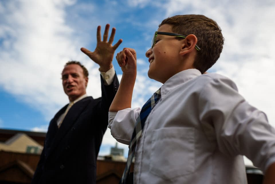 Man giving high five to kid at wedding