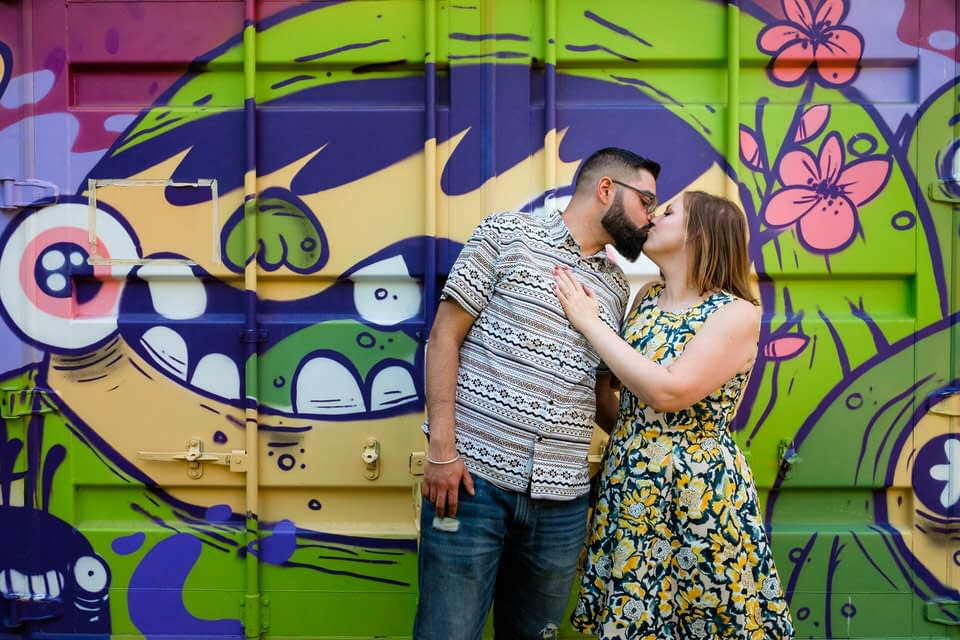 Engaged couple in front of graffiti in park