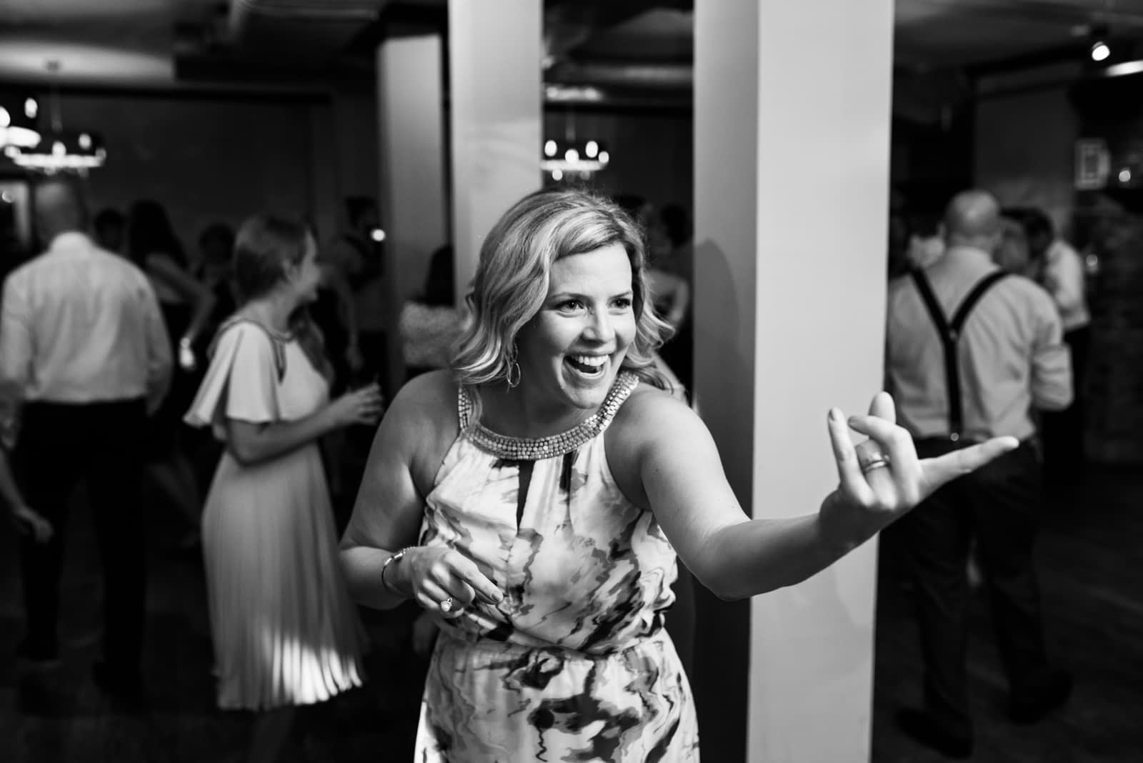 Wedding guests gesturing to friend to come and dance with her