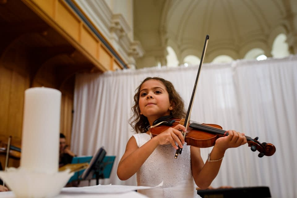 Bride's daughter playing violin at kid-friendly wedding ceremony