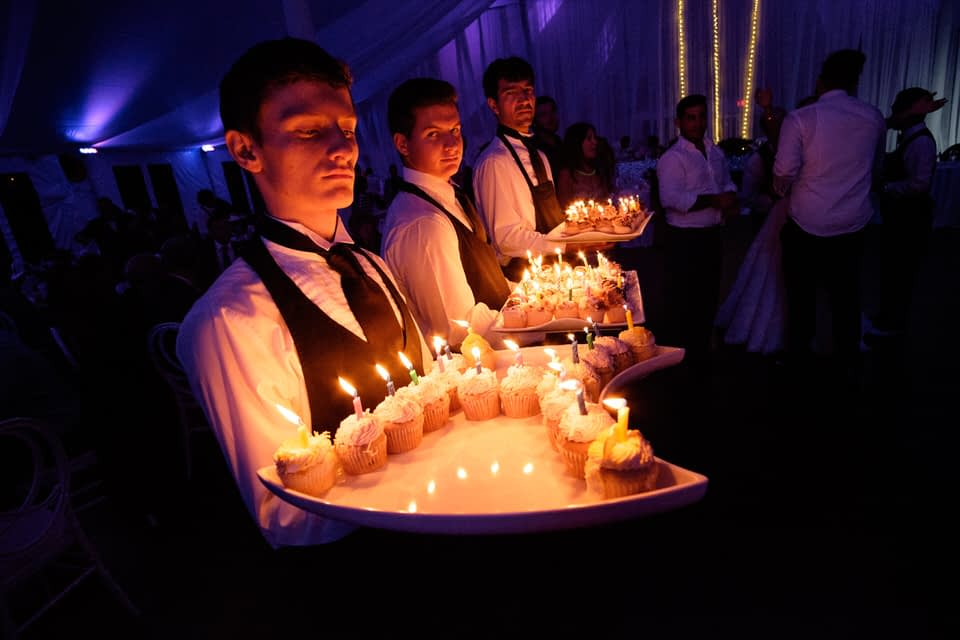Venue staff carrying birthday cupcakes out