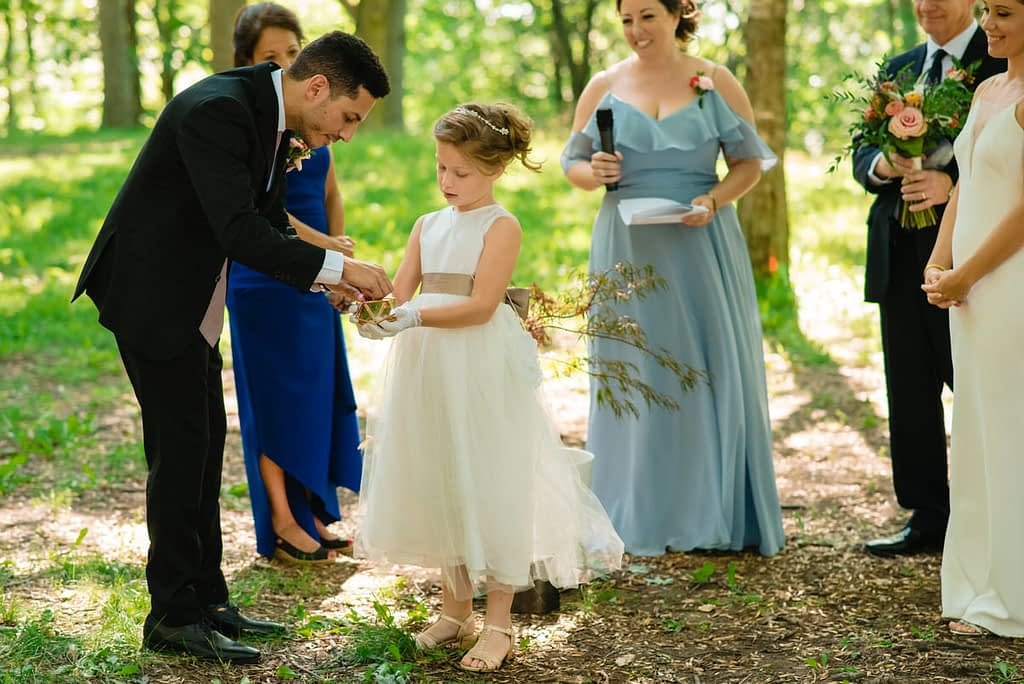 The bride's daughter carrying the rings to the groom