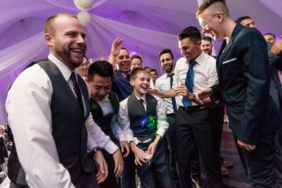 Everyone laughing as a young boy has caught the garter belt