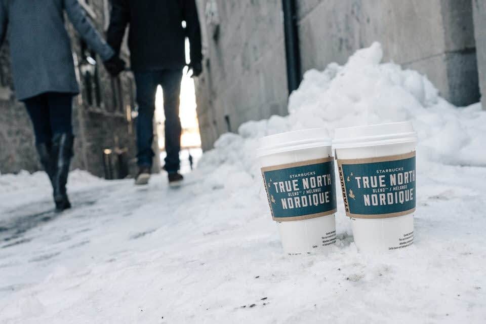 Close up of two cup of coffee in the snow as a couple walks away