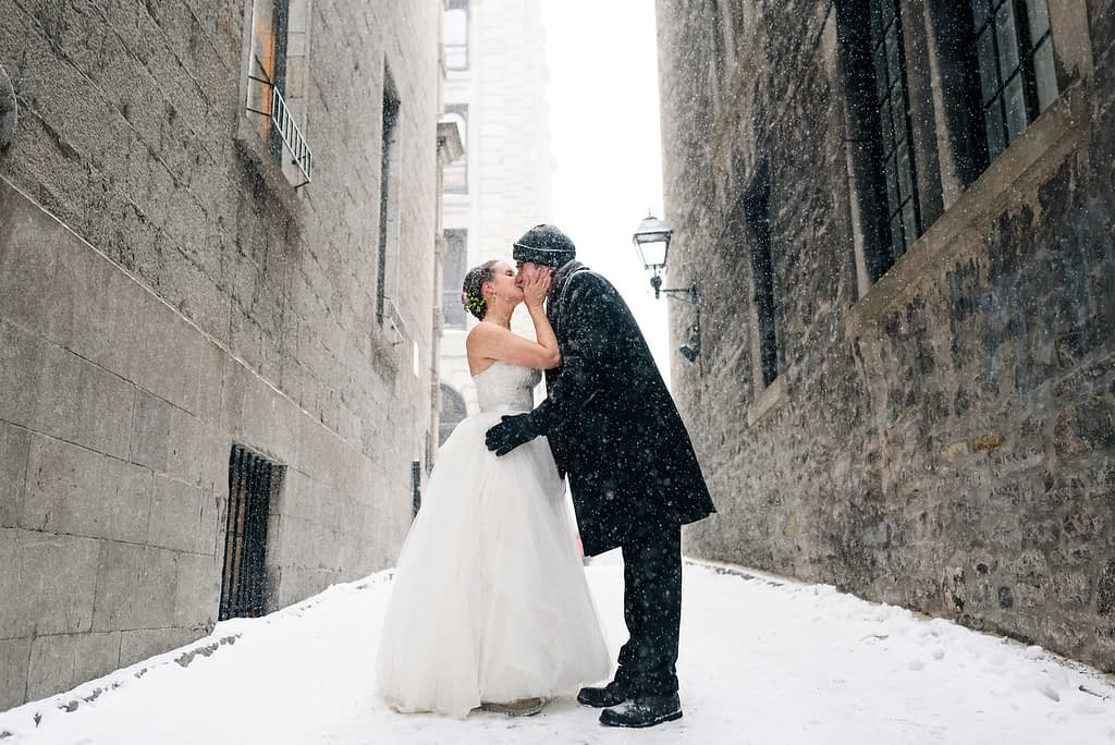 Winter wedding in Old Montreal as couple kisses in the snow