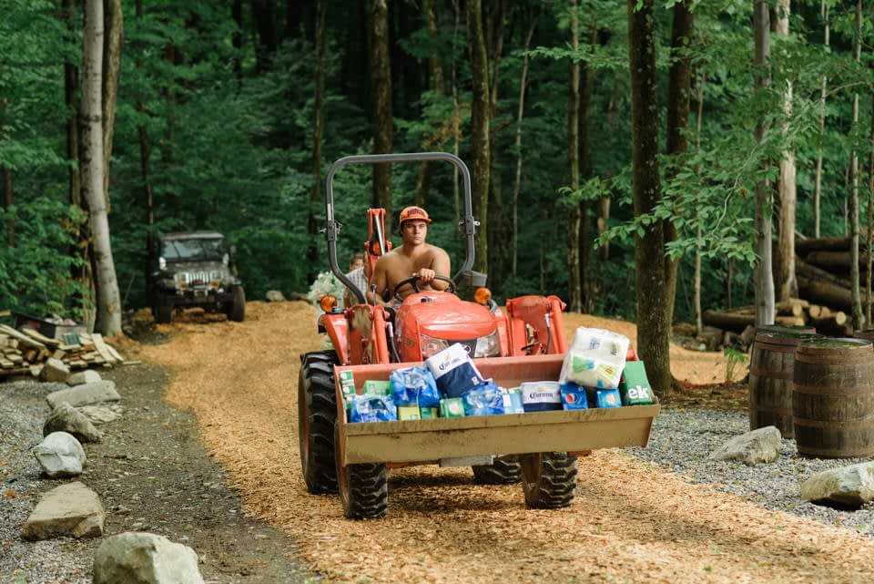 Man driving small tractor carrying wedding party supplies up a gravel road on a hill