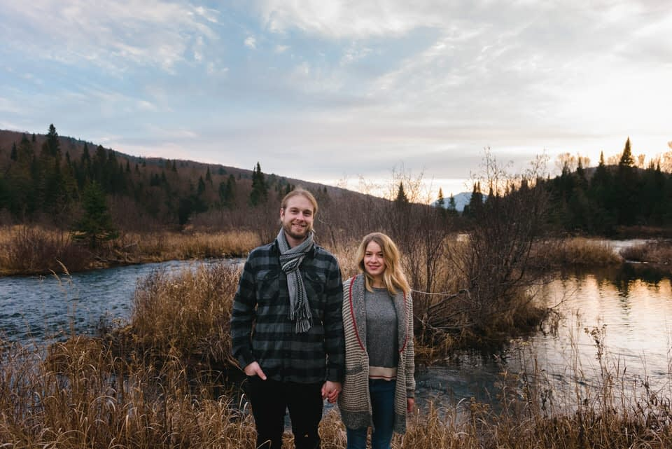 Engaged couple holding hands in front of wild landscape at Mont-Tremblant