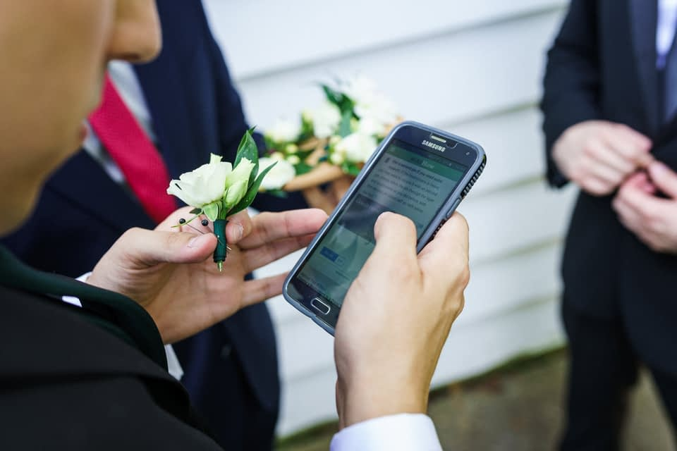 Groomsmen looking up video on how to pin flower on