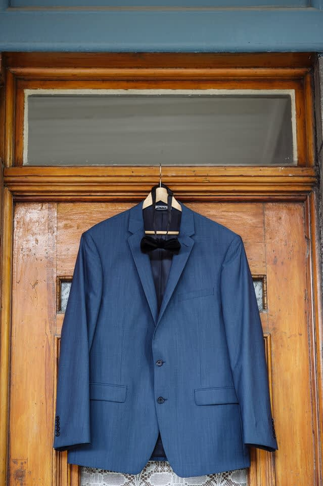 Groom's suit hanging on his doorway