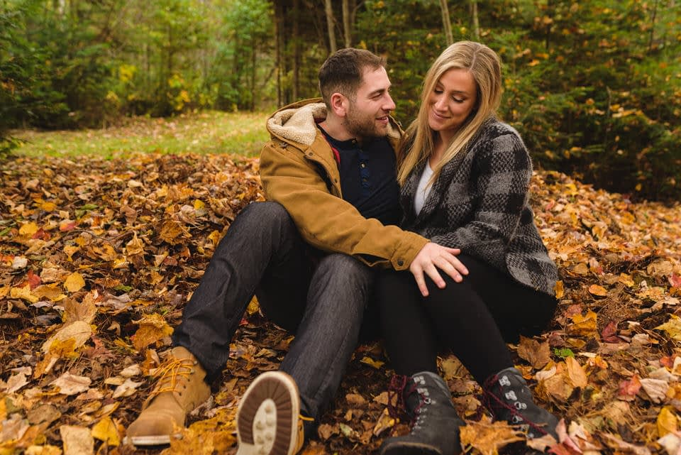 Engaged couple sitting in fall leaves