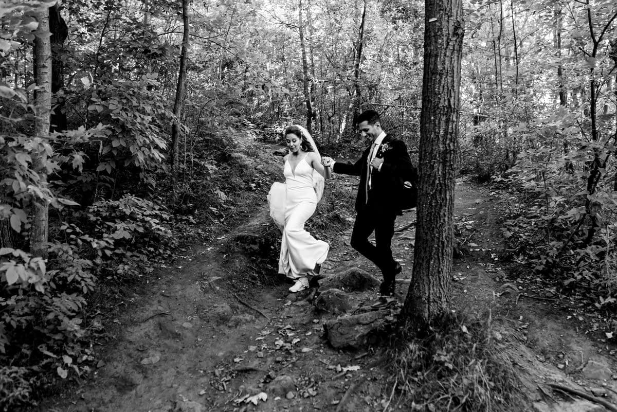 Groom leading bride down a rocky path through the woods