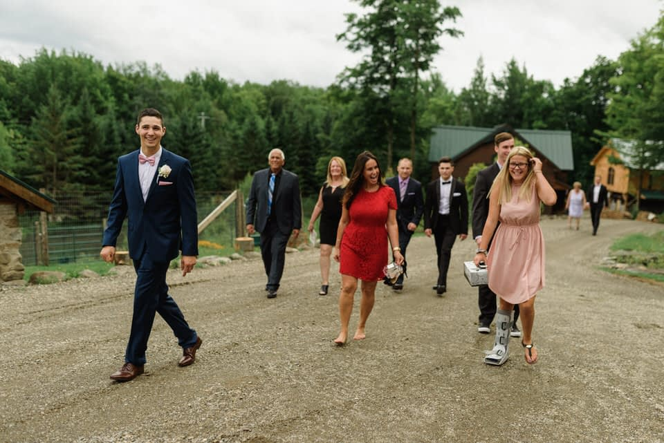 Groom walking up a gravel road with wedding guests including a woman in a boot cast