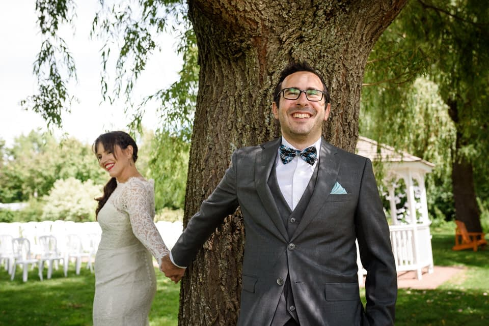 Groom and bride holding hands without looking at each other