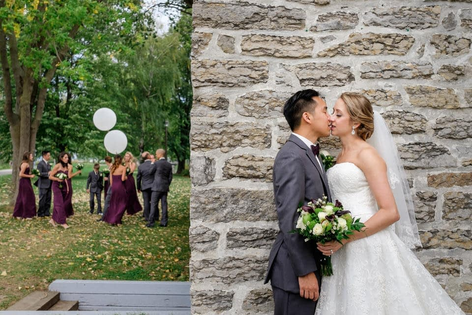 Bride and groom kissing behind building with wedding party behind