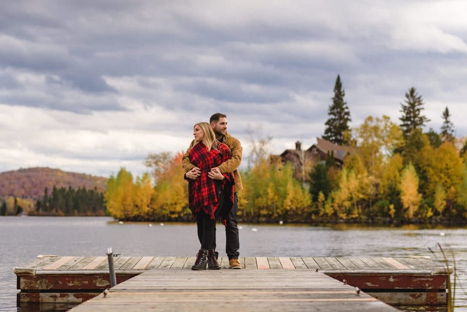 Couple hugging on dock with view of lake behind