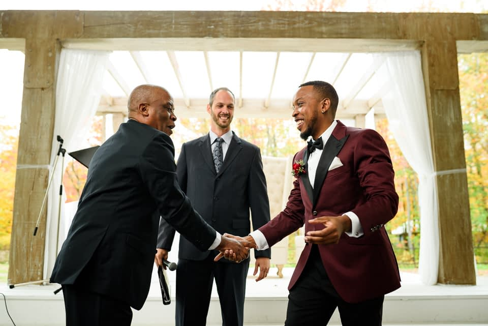 Groom and father shaking hands at wedding ceremony