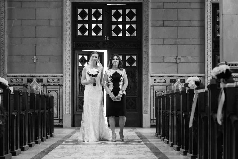 bride and her mother walking up the church aisle