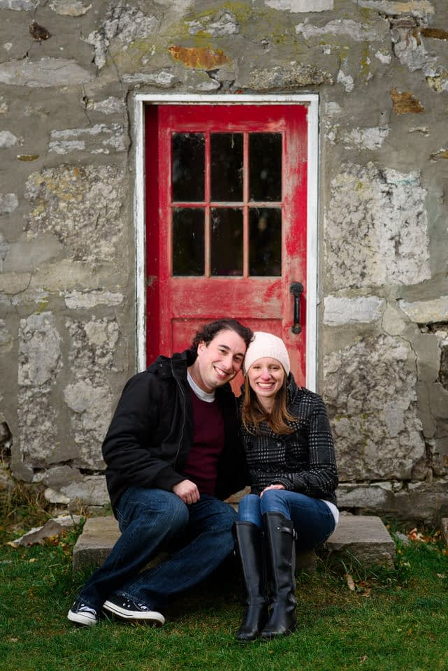 Engaged couple sitting and posing in front Pointe-Claire windmill door