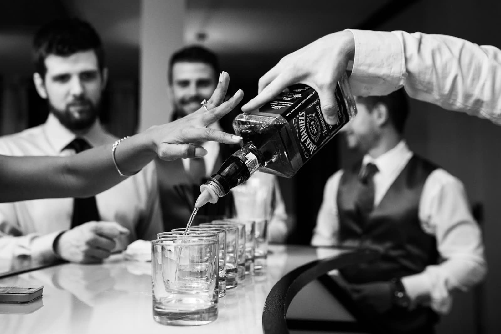 Wedding guest pushing whiskey bottle down to get more booze