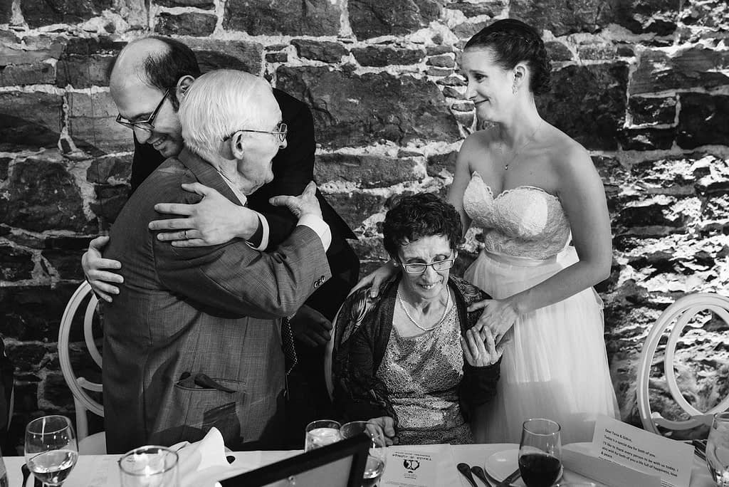 Groom hugging the bride's grandfather as she looks on